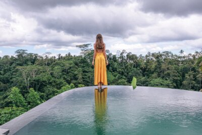 Plakat beautiful woman with dark hair in elegant yellow dress posing on the edge of the pool with jungle view