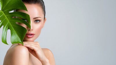 Plakat Beautiful woman with green leave near face and body.  Closeup girl's face with green leave. Skin care beauty treatments concept.