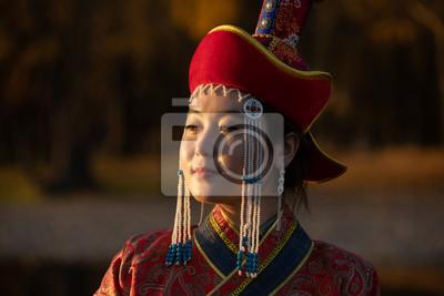 Plakat Beautiful young woman posing in traditional Mongolian dress in sunset light. Ulaanbaatar, Mongolia.