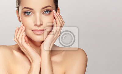 Plakat Beautiful young woman with clean fresh skin on face . Girl facial  treatment   . Cosmetology , beauty  and spa .