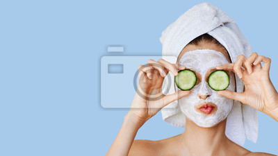 Plakat Beautiful young woman with facial mask on her face holding slices of cucumber. Skin care and treatment, spa, natural beauty and cosmetology concept.