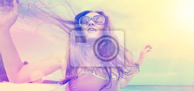beztroski młoda kobieta tańczy w zachodzie słońca na plaży.