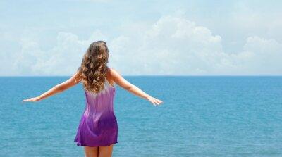 Beztroski szczęśliwa kobieta w sukni i wolnych otwartych ramion na wybrzeżu w słoneczny dzień.