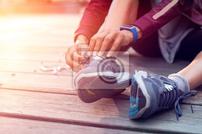Plakat Biegacz wiążący buty sportowe