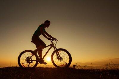 Plakat Biker-girl na zachód słońca w górach