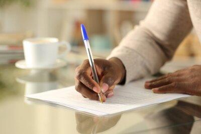 Plakat Black man hands filling out form on a desk