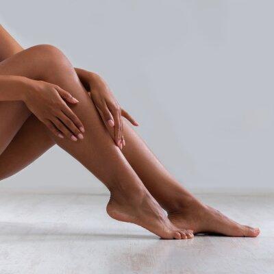 Plakat Black woman touching silky skin on her legs