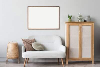 Plakat Blank picture frame mockup on gray wall. Artwork in interior design. View of modern scandinavian style interior with sofa and empty canvas for painting or poster on wall. Minimalism concept