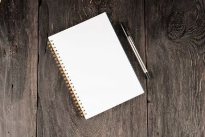 Plakat blank sheet in notebook for notes on a wooden table as a business concept.