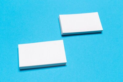 Plakat Blank white business cards on blue background. Mockup for branding identity. Template for graphic designers portfolios. Top view.