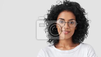 Plakat Bliska portret kędzierzawej dorosłej kobiety ma czarujący uśmiech, kręcone ciemne włosy, nosi duże okulary, zadowolony z ukończonej pracy domowej wcześniej, jako odnoszący sukcesy projektant lub archi