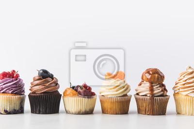 Plakat bliska widok różnych słodkie babeczki na białym