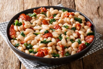 Plakat Boiled beans with spinach, garlic and dried tomatoes close-up on a plate. horizontal