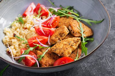 Boiled bulgur, roasted chicken nuggets and fresh tomatoes salad. Middle eastern cuisine.