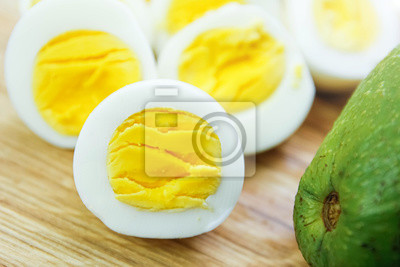 Plakat boiled eggs with avocado on a wooden board.
