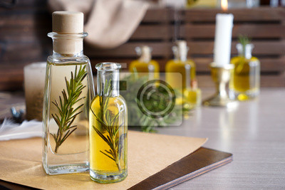 Plakat Bottles of rosemary oil on table