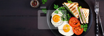 Breakfast: fried egg, spinach, tomatoes and club sandwich on plate. Top view, banner