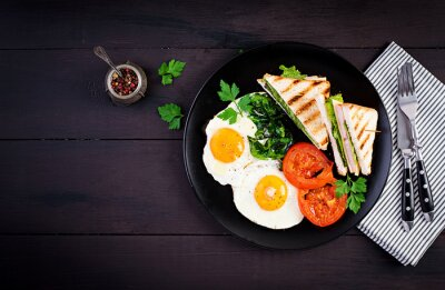 Breakfast: fried egg, spinach, tomatoes and club sandwich on plate. Top view, copy space