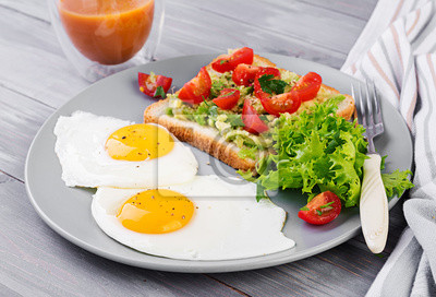 Breakfast. Fried egg, vegetable salad and a grilled avocado sandwich on a grey background.