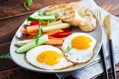 Breakfast. Fried eggs with fresh carrot, cucumber, paprika and toast on wooden background. Vegetarian meal.