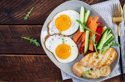 Breakfast. Fried eggs with fresh carrot, cucumber, paprika and toast on wooden background. Vegetarian meal. Top view, copy space