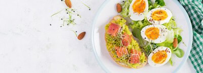 Breakfast. Healthy open sandwich on  toast with avocado and salmon, boiled eggs, herbs, chia seeds on white plate  with copy space. Healthy protein food. Top view, banner
