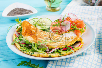 Breakfast. Omelette with radish, green arugula and sandwich with salmon on white plate.  Frittata - italian omelet.