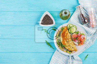 Breakfast. Omelette with radish, green arugula and sandwich with salmon on white plate.  Frittata - italian omelet. Top view