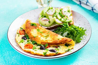 Breakfast. Omelette with tomatoes, black olives and sandwich with avocado on white plate.  Frittata - italian omelet.