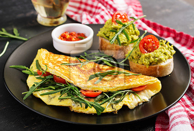 Breakfast. Omelette with tomatoes, cheese, green arugula and toasts with avocado cream on black plate. Frittata - italian omelet.