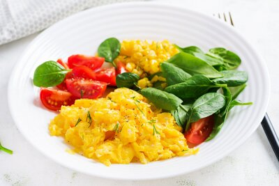 Breakfast. Scrambled eggs with cherry tomatoes, spinach  and corn.
