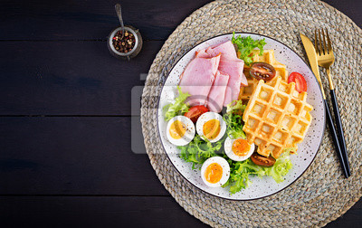 Breakfast with cornmeal waffles, boiled egg, ham and tomato on dark background. Appetizers, snack, brunch. Healthy food. Top view, overhead, copy space