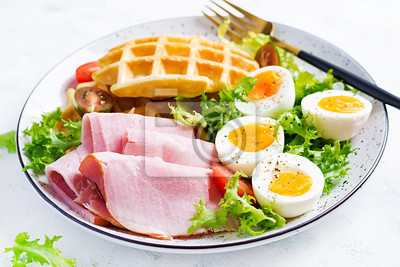 Breakfast with cornmeal waffles, boiled egg, ham and tomato on white background. Appetizers, snack, brunch. Healthy food.