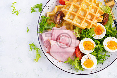 Breakfast with cornmeal waffles, boiled egg, ham and tomato on white background. Appetizers, snack, brunch. Healthy food. Top view, overhead, copy space