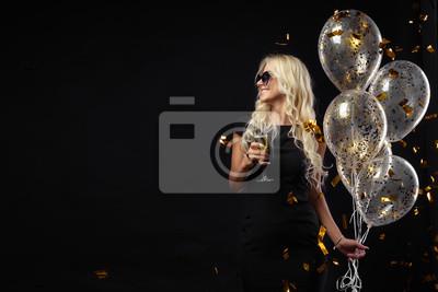 Plakat Brightfull wyrażenia szczęśliwych emocji niesamowitej blondynki świętuje przyjęcie na czarnym tle. Luksusowe czarne sukienki, uśmiechnięte, kieliszek szampana, złote blaszki, balony, długie kręcone wł
