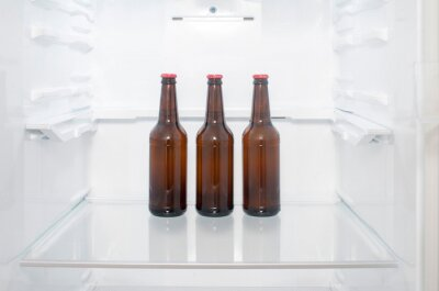Plakat Brown glass beer bottles stand on a shelf in the refrigerator
