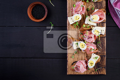 Bruschetta with prosciutto/jamon traditional Italian antipasto. Delicious snack with bread, brie cheese and quails eggs. Health food, tapas. Top view, copy space