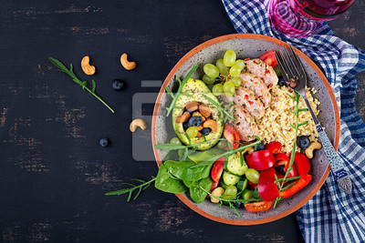 Buddha bowl dish with meatloaf, bulgur, avocado, sweet pepper, tomato, cucumber, berries and nuts. Detox and healthy superfoods bowl concept. Overhead, top view, flat lay
