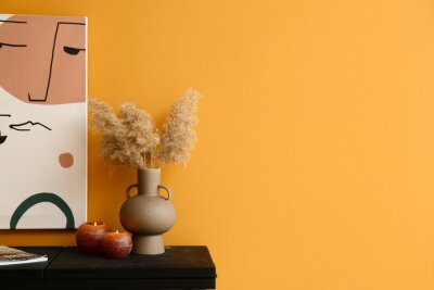 Plakat Burning candles with vase on table near color wall