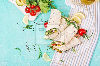 Burritos opakowuje się z kurczakiem i warzywami na jasnym tle. Kurczak burrito, meksykańskie jedzenie. Widok z góry, płasko układany