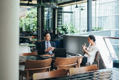 Plakat Business colleagues discussing work at office cafeteria.  Businessman and businesswoman sitting at cafe and talking about investment ideas and cooperation plans together
