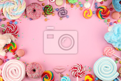 Plakat candies with jelly and sugar. colorful array of different childs sweets and treats on pink
