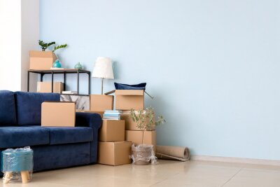Plakat Cardboard boxes with belongings and sofa in new flat on moving day