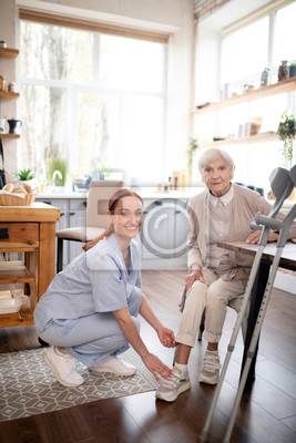 Plakat Caregiver smiling while helping aged woman to lace shoes