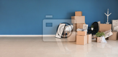 Plakat Carton boxes and interior items prepared for moving into new house near color wall