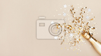 Plakat Celebration background with golden champagne bottle, confetti stars and party streamers. Christmas, birthday or wedding concept. Flat lay.