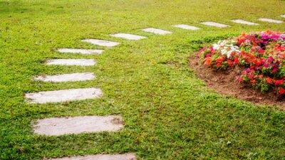 Plakat cement walkway in a flower garden.