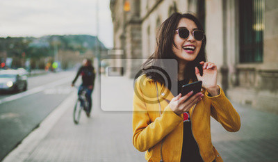 Plakat Cheerful asian student girl wearing modern sunglasses laughing at friends' photos in social media by a mobile phone. Happy model look woman in casual outfit checking blog comments via smartphone.