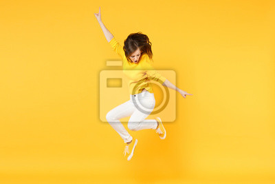 Plakat Cheerful funny young woman in summer casual clothes jumping and spreading hands isolated on yellow orange wall background in studio. People sincere emotions, lifestyle concept. Mock up copy space.