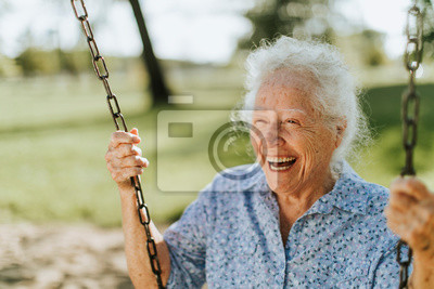 Plakat Cheerful senior woman on a swing at a playground
